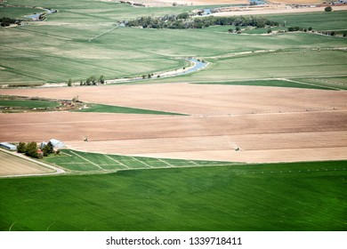 An aerial view of two tractors planting potatoes in the fertile farm fields of Idaho