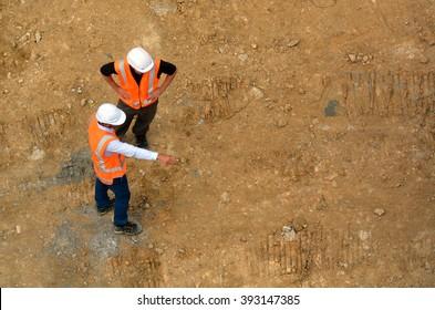 Luftaufnahme von zwei nicht anerkannten Ingenieuren, die Baustellen inspizieren. Baukonzept mit Kopienraum