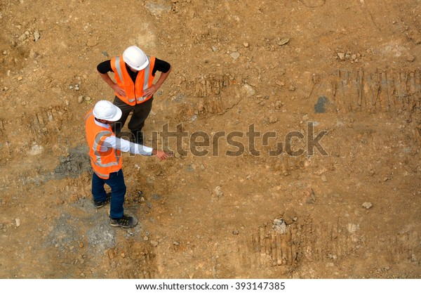 Aerial view of two unrecognized civil engineers inspecting construction site. Building development concept with copy space