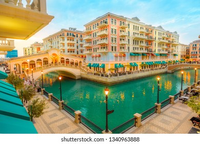 Aerial view of two Venetian bridges on canals of picturesque and luxurious district of Doha illuminated at blue hour. Scenic Venice at Qanat Quartier in the Pearl-Qatar, Persian Gulf, Middle East.