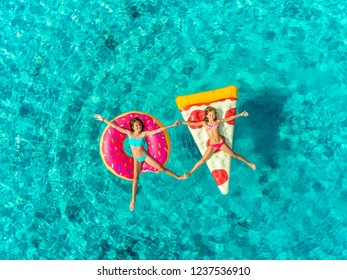 Aerial view of two young girls floating in sea on pizza and donut shaped inflatable holding hands, touching feet and smiling.