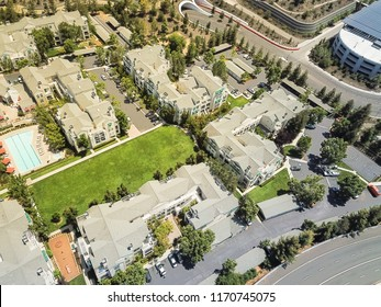Aerial view typical multi-level apartment homes with swimming pool near freeway in Silicon Valley, California