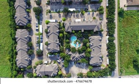 Aerial view typical multi-level apartment building complex with swimming pool, surrounded green garden and rows of cars in parking lots in Houston, Texas, US. Residential recreation concept. Panorama.