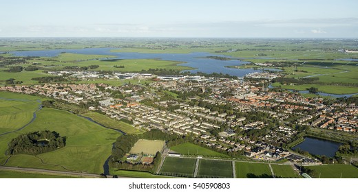 Aerial view of Uitgeest, a small village in the Netherlands at Lake Uitgeestermeer and Lake Alkmaardermeer. There is a blue sky, clear horizon and green meadows surrounding the town.