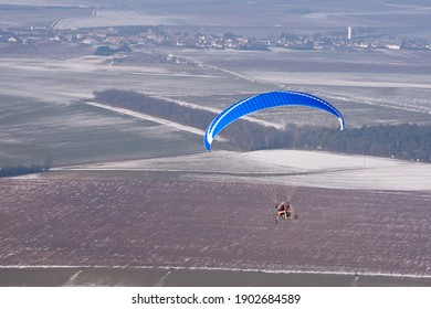 Vue aérienne d'un paramoteur ULM volant en hiver dans un paysage enneigé en hiver