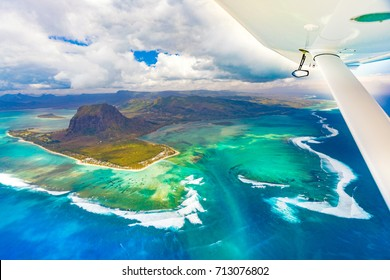 Aerial view of the underwater waterfall. Plane wing on the foreground. Mauritius