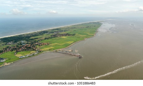 Aerial view of the UNESCO protected island Ameland, Netherlands, in the Dutch sea Waddenzee. It is a beautiful day with a clear horizon with some clouds. The ferry is just arriving in the harbour.