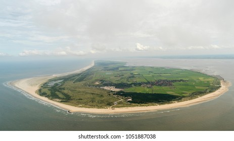 Aerial view of the UNESCO protected island Ameland, Netherlands, in the Dutch sea Waddenzee. It is a beautiful day with a clear horizon with some cumulus clouds.