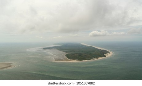 Aerial view of the UNESCO protected island Terschelling, Netherlands, in the Dutch sea Waddenzee. It is a beautiful day with a clear horizon with some clouds. The green nature area is Boschplaat.