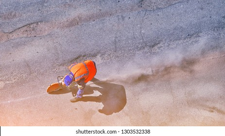 Aerial view of unrecognizable road builder worker cutting asphalt or concrete with saw blade at construction site. cut-off machine power tool breaking asphalt. Lots of dust from cutting.