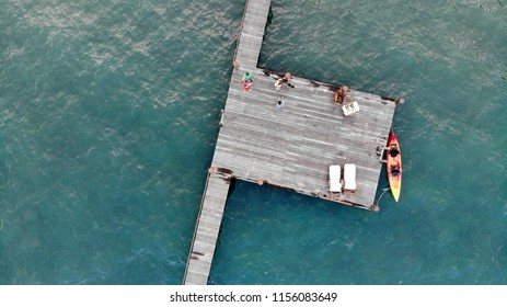 Aerial view of unrecognizable young people in a kayak near a boat pier in Lake Tahoe