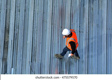 Aerial view of unrecognized civil engineer inspecting the work progress in a construction site. Building development concept with copy space