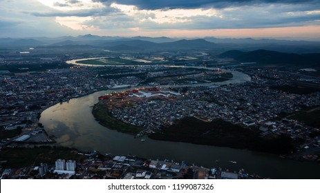 Aerial view of urban areas along a meandering river during sunset, with mountains in the background (Itajai and Navegantes, Brazil)