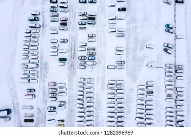 aerial view of urban parking lot covered with fresh snow in winter