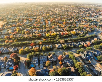 Aerial view urban sprawl with colorful fall foliage near Dallas, Texas, USA. Flyover suburban subdivision with row of residential single-family houses and apartment complex buildings in autumn morning