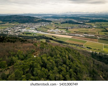 Aerial view urban sprawl in Switzerland above highway intersection in Egerkingen and Swiss Alps in background during Spring. Concept: Close, Nature, Transportation, space, planning, lack of space