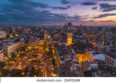 Aerial view of Valencia, Spain at sunset. Illuminated Plaza de la Reina with many cafes and restaurants and very popular among tourists. Cloudy colorful sky