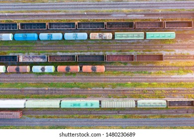 Aerial view of various railway carriage trains with goods on the railway station, top view.