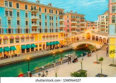 Aerial view of Venetian bridge and canals of picturesque and luxurious district of Doha illuminated at twilight. Scenary of Venice at Qanat Quartier in the Pearl-Qatar, Persian Gulf, Middle East.