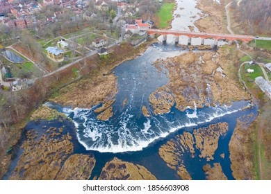 Aerial view of Venta Rapid (Ventas Rumba) waterfall. Widest waterfall in Europe and The Old Brick Bridge across the Venta river in Kuldiga