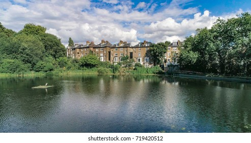 Aerial view of Victorian houses reflecting on a pond in a park in North London