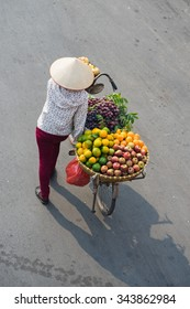 Aerial view of Vietnamese vendor with tropical fruit loaded basket on bike