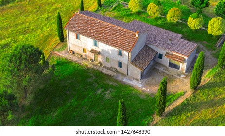 Aerial view of a villa at sunset. The country house has a large garden with trees and plants and is surrounded by nature in the hills of Tuscany, Italy.
