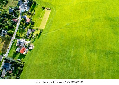 Aerial view of a village and a big green meadow