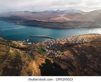 Aerial view of the village Eidi with snow-covered mountain range, football field and dramatic sky during sunset (Faroe Islands, Denmark, Europe)