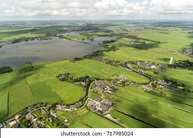 Aerial view of village Meije (holland) and nature reserve area at the Niewkoopse Plassen. Dutch houses, green fields, lakes and a crystal clear sky with cumulus clouds and cloud shadows on the ground