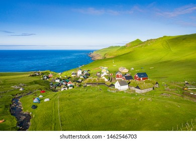 Aerial view of village at Mykines island in Faroe Islands, North Atlantic Ocean. Photo made by drone from above. Nordic natural landscape.