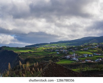 Aerial view of village Santana with lush green fields, trees and hills and from viewpoint Miradouro de Andro da Ingreja, cloudy day, Nordeste, Sao Miguel island of Azores, Portugal