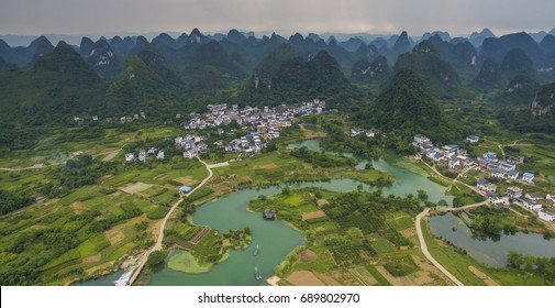 Aerial view of a village surrounded by karst and padi fields in Yongshua County China