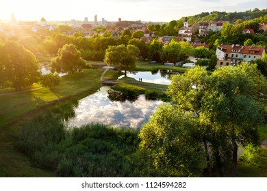 Aerial view of Vilnius cityscape shot from Subaciaus viewpoint on sunset. Clouds reflecting in three little ponds of Lithuania capital's city park.