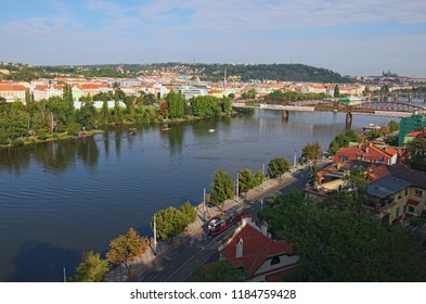 Aerial view to Vltava river with Vysehrad Railway Bridge and Prague Castle with Saint Vitus Cathedral at the background. Beautiful blue cloudy sky. View from popular view point. Summer morning.