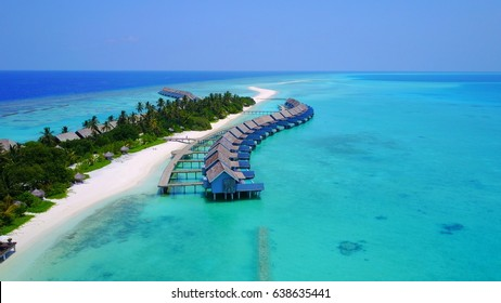 Aerial view of water bungalow and blue sea sky background in Maldives