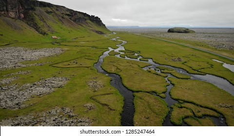 Aerial view of water flows finding their way through green meadows in a valley near Kirkjubæjarklaustur, Iceland. Panoramic landscape shot by drone camera.