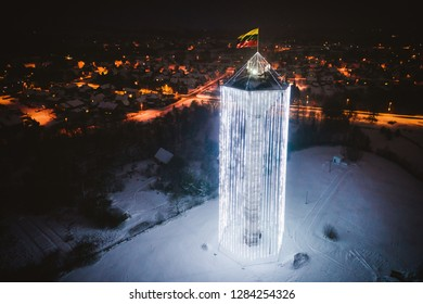 Aerial view of water tower decorated with Christmas lights and Lithuanian flag in Pasvalys city at night.