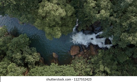 Aerial view of a waterfall in the middle of a jungle surrounded by trees (Kahanavita Ella Waterfall, Sri Lanka)