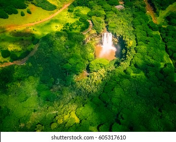Aerial View of Waterfall surrounded by Green Forest in Kauai Island, Hawaii.