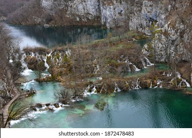 Aerial view of waterfalls rushing over rocks overgrown with moss. It is winter and the water has a green tinge. The hills are bare rock. The water is so clear we can see the difference in depth.