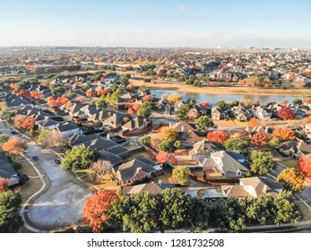 Aerial view waterfront residential subdivision with cul-de-sac dead-end street in suburban Dallas, Texas. Urban sprawl with row of single-family houses and colorful fall leaves, blue sky