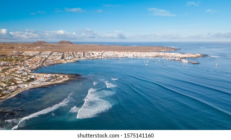 aerial view of waves crashing on the bay of corralejo, fuerteventura