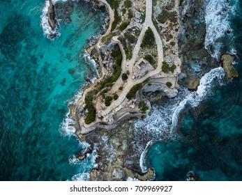 Aerial view of waves crashing on Punta Sur - Isla Mujeres, Mexico - with brilliant blue water, crashing waves and rocky shoreline.