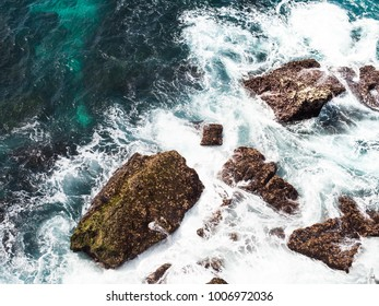 Aerial view of waves crashing the rocky shoreline