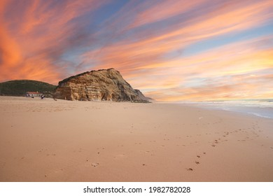 Aerial view of waves on a beautiful sandy ocean beach and cliff at the sunset. Panorama atlantic coastline.