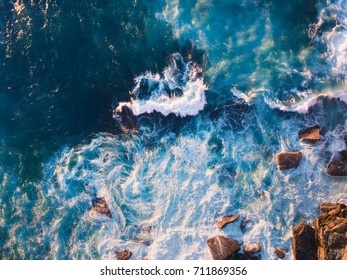 Aerial view of waves and some of rocks.