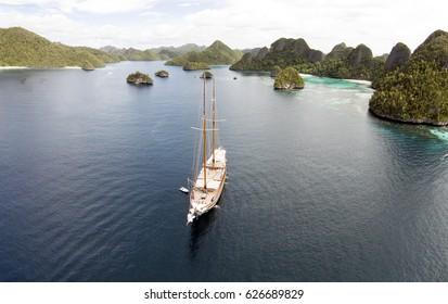 Aerial view of Wayag Island and sailing yacht Lamima, Raja Ampat Indonesia