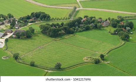 Aerial view of Westsens, Holland, a small village in the province of Friesland. The town is built on a mound or terp. It is a green landscape with a circle pattern, some houses and a farm.