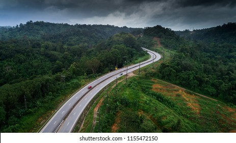 Aerial view of wet highway road in green forest mountain in rainy season